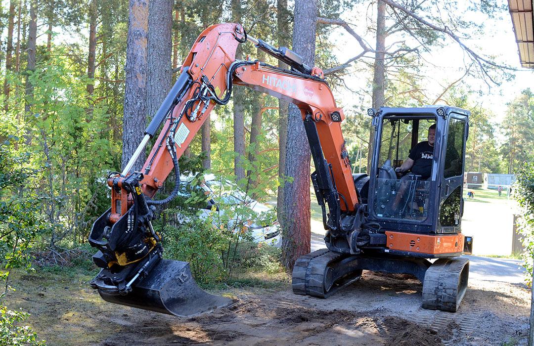 Kaivinkoneurakoitsija Jarkko Salminen peittelee ja siistii kanaalikaivannon jäljet rivitalon pihalla.