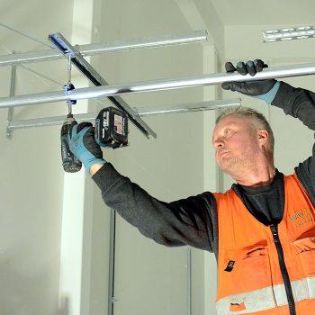 LVI-asentaja Kimmo Jalava asentaa koulun ja päiväkodin yhteisessä teknisessä tilassa putkien kiinnikkeitä.